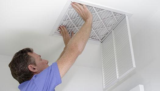 Man installing a HVAC filter.