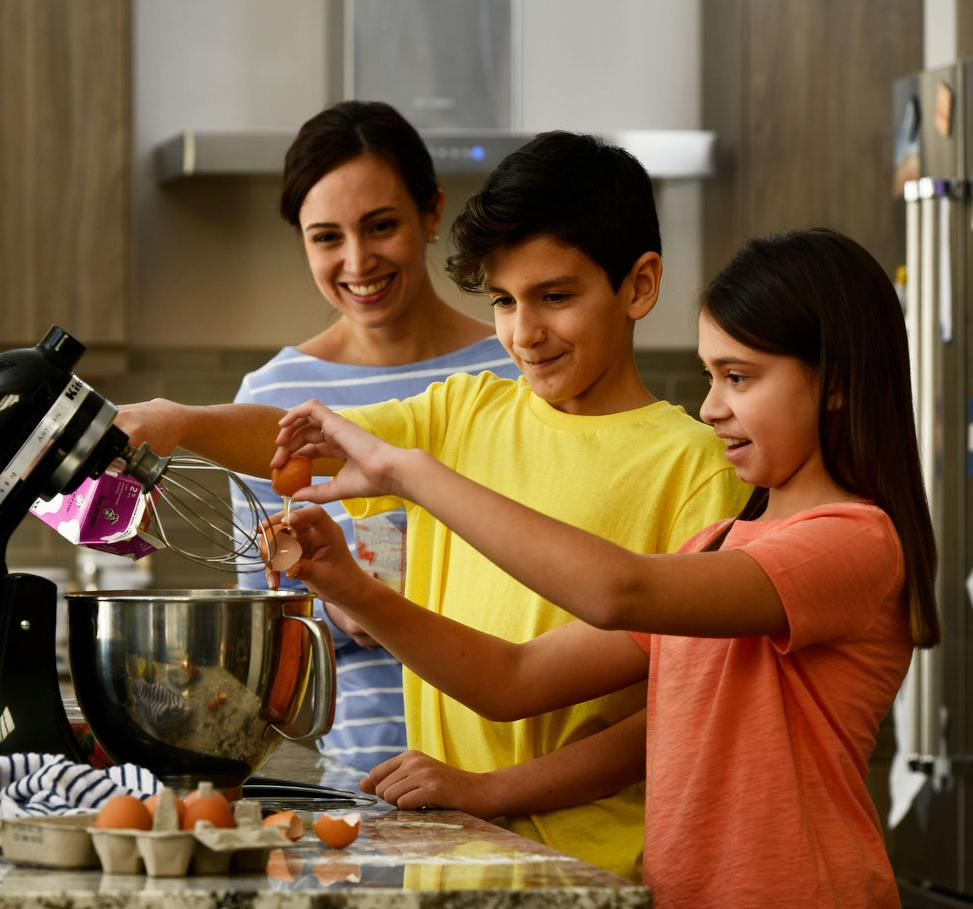 Mother helping kids use stand mixer