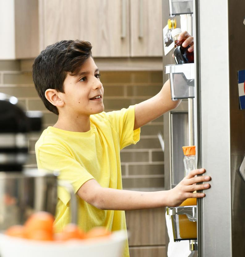 Boy getting a drink from the fridge