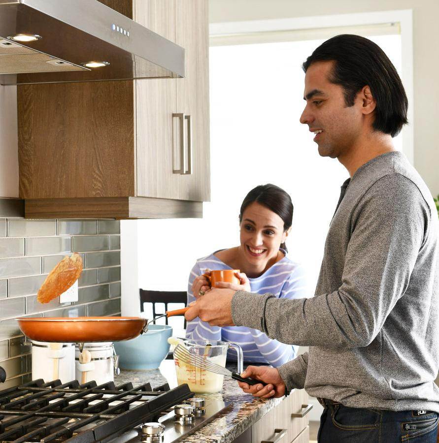 Man cooking pancakes while his wife watches