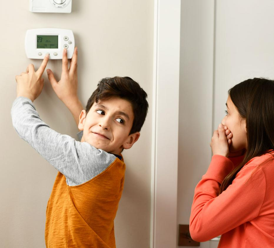 Children adjusting a thermostat