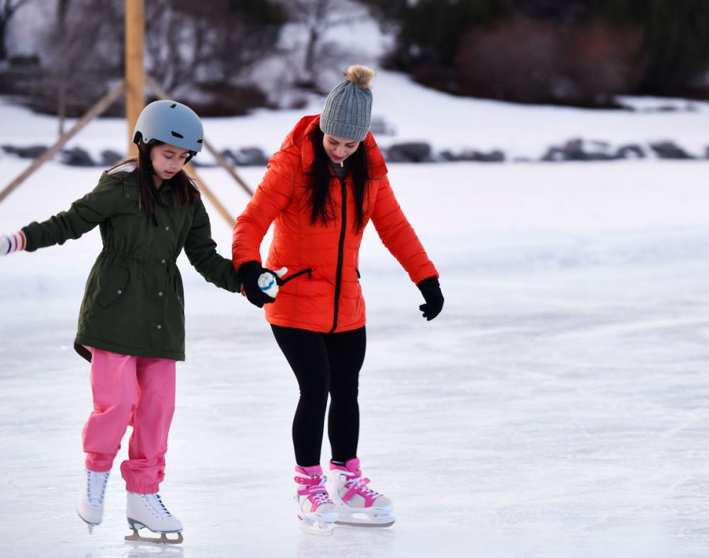 Mom and daughter skating on a frozen lake