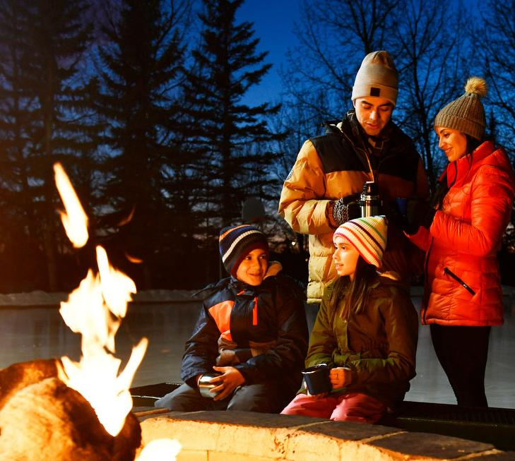 Family sitting around an outdoor fire