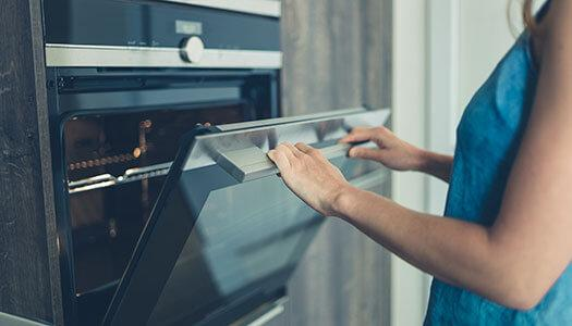 Woman opening an oven door.