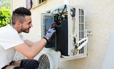 A young man repairs the air conditioning unit outside his home.