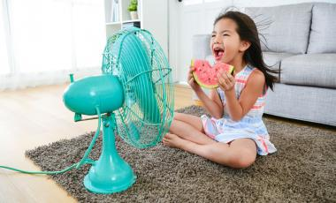 A young girl is holding watermelon sitting in front of electric fan blowing cool air in her home on a hot summer day.