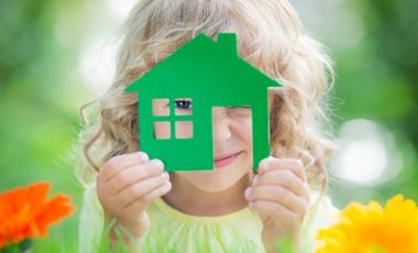 Little blond girl holding a green toy house to her face.