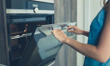 Woman opening an oven door.