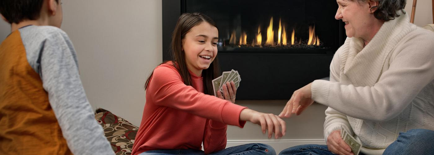 A family playing cards in front of a gas fireplace