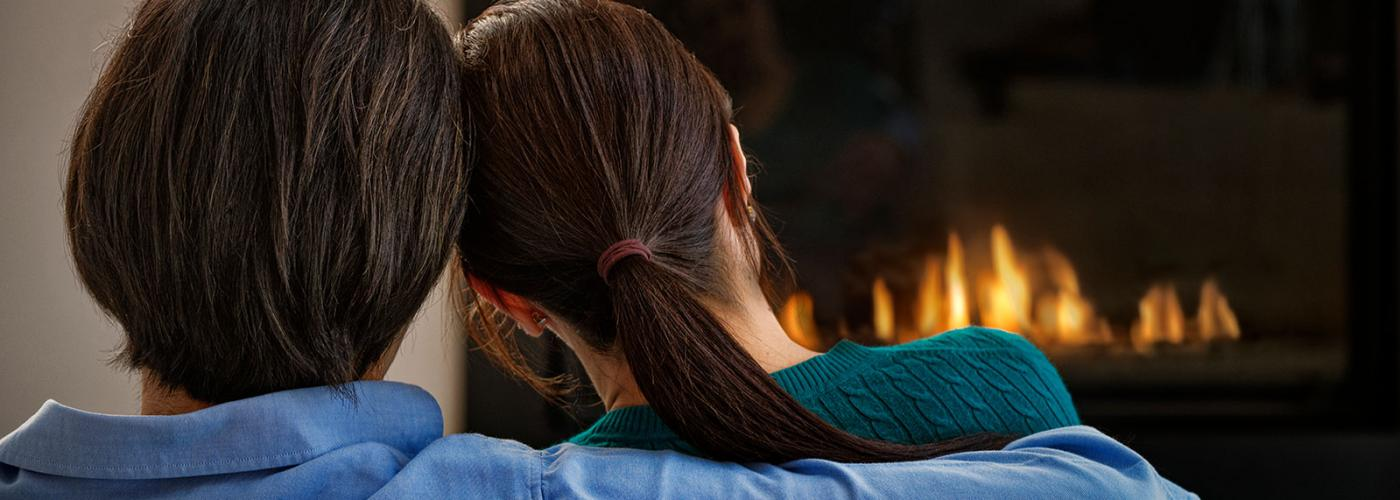 Couple sitting in front of a gas fireplace