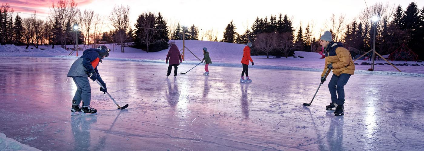 Kids playing hockey on an outdoor rink