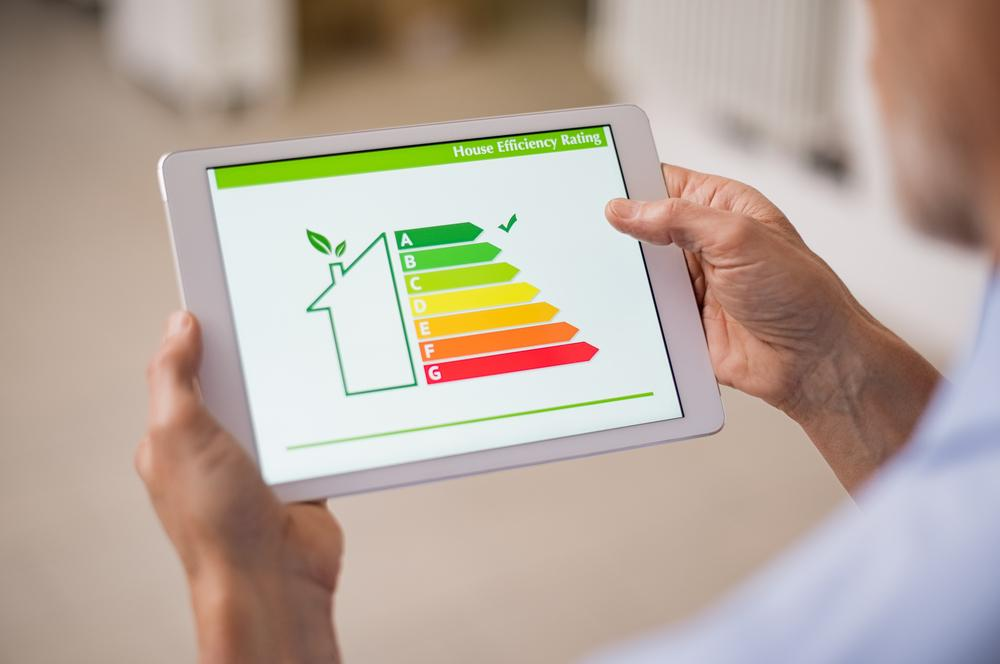 Man holding tablet showing energy measurement in home