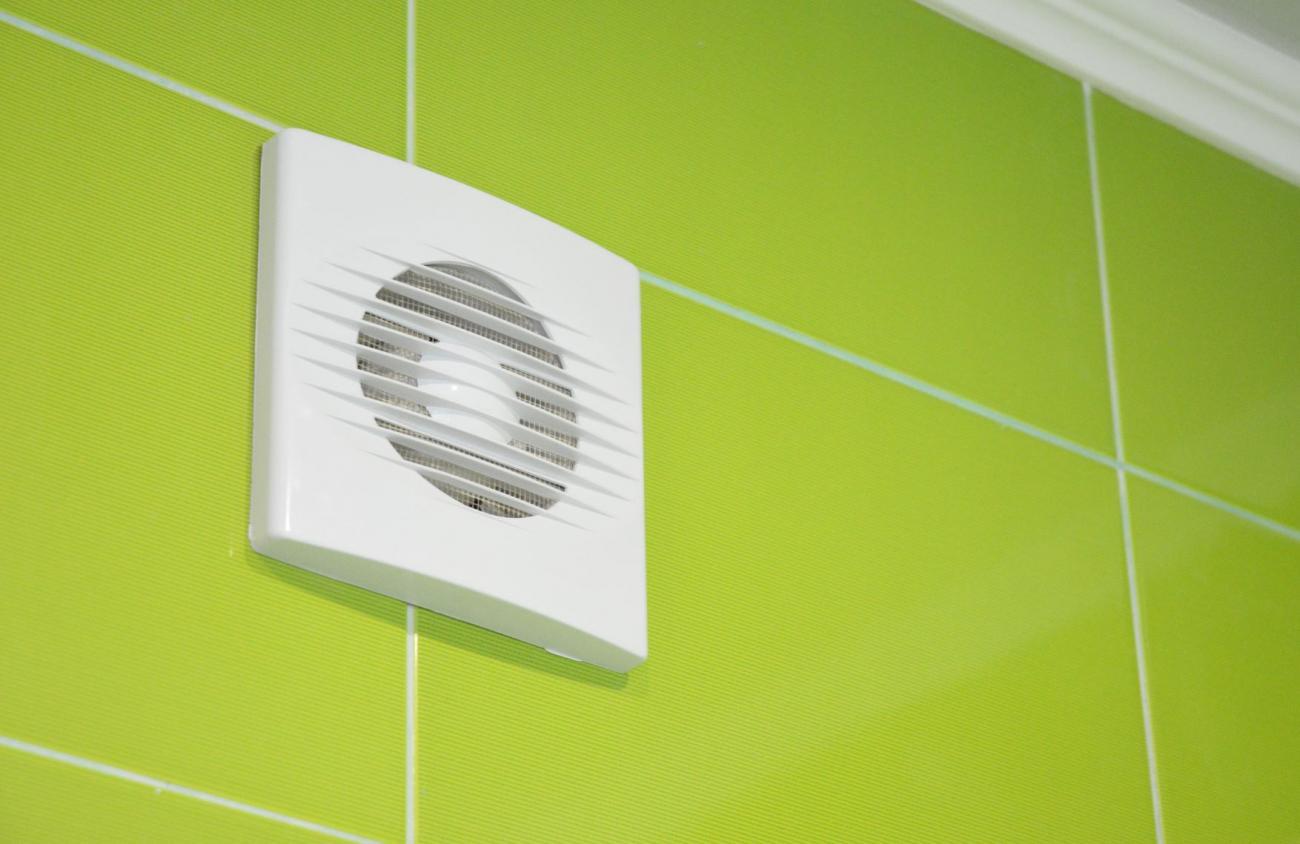 Bathroom fan on tiled bathroom wall