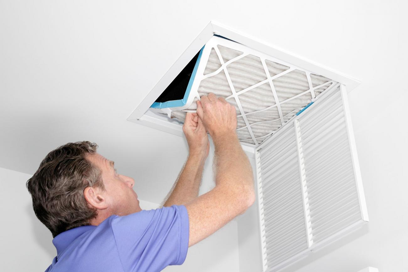 A man changes out his home's air filter.