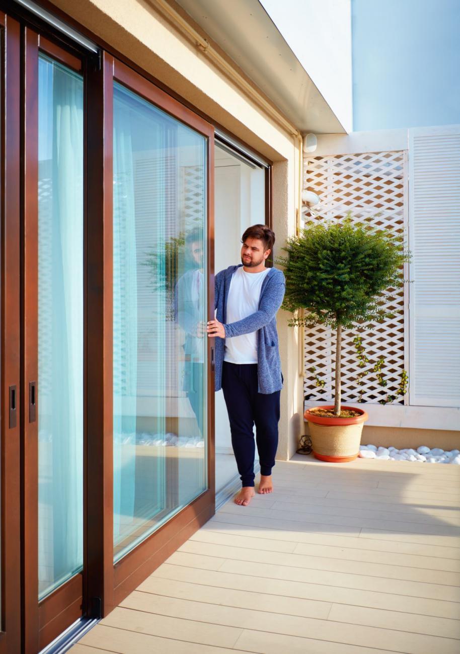 Man examines his home's sliding glass doors.