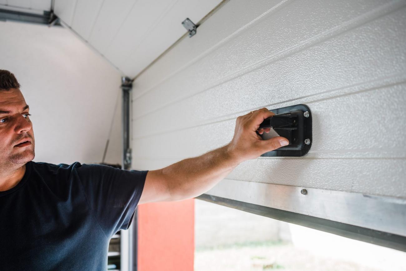Man checks the weather stripping on his garage