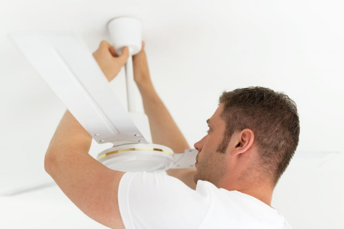 Man adjusts his ceiling fan for spring