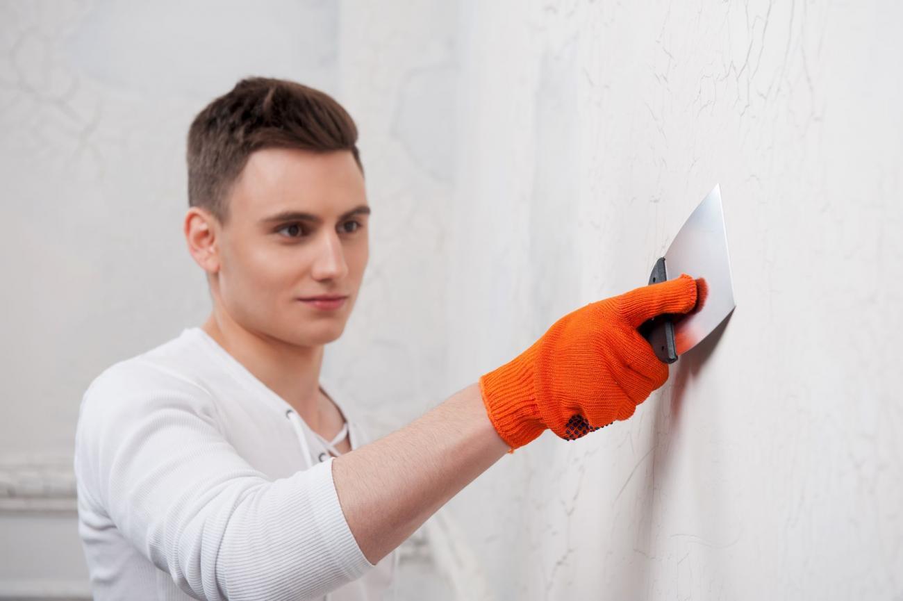 Man sealing cracks in the walls.
