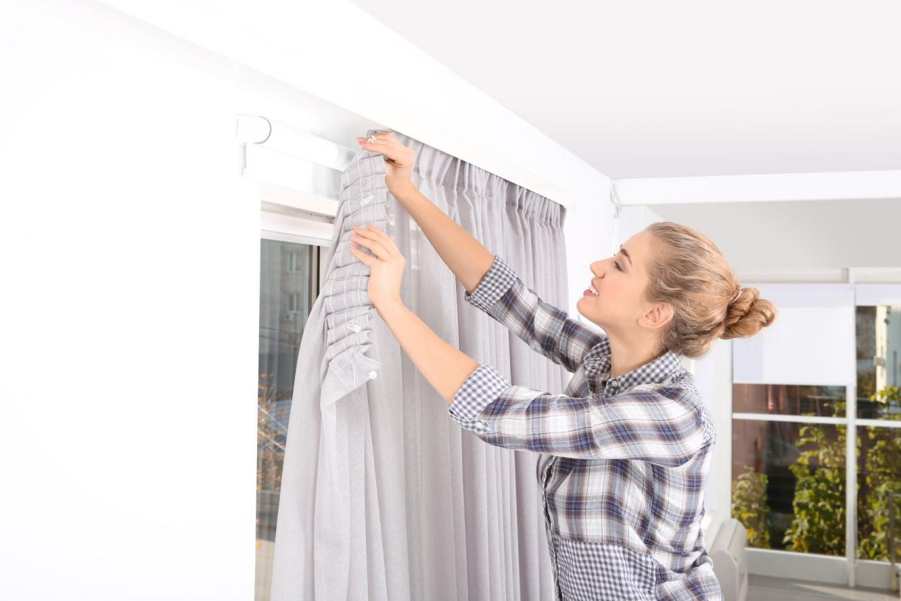 Woman installing blackout curtains in her home